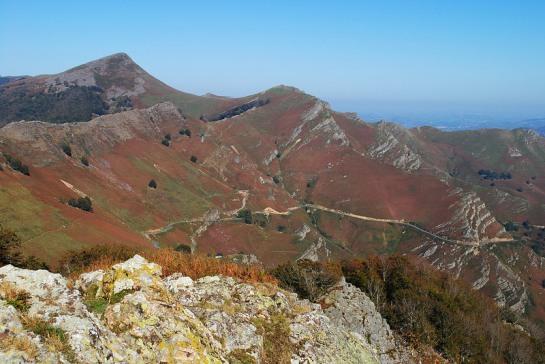 Au Nord-Est, le pic de Buztanzelhay (1029m) marque le début des crêtes d'Iparla qui s'étirent loin vers le Nord, presque jusqu'à Bidarray. On voit bien la balafre de la route du col, à flanc de montagne.